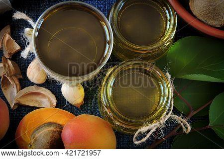 Jars Of Apricot Kernel Oil. Apricots, Leaves, Seeds.