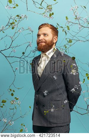 Portrait Of Young Red Headed And Bearded Man Acting Famous Artist Isolated Over Blue Floral Bacgroun