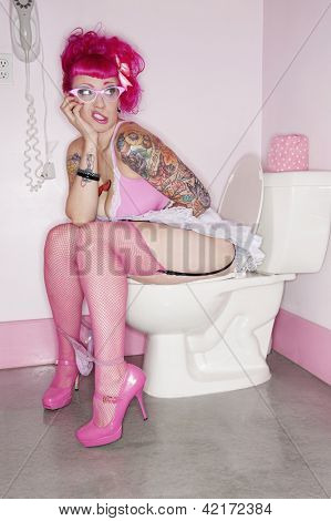 Tattooed woman sitting on toilet seat with her panties down