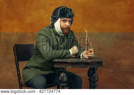 Portrait Of Red Headed And Bearded Man Playing Famous Artist Isolated Over Dark Bacground