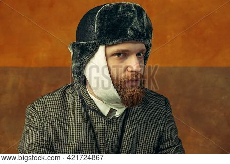 Close-up Portrait Of Red Headed And Bearded Man Playing Famous Artist Isolated Over Dark Bacground