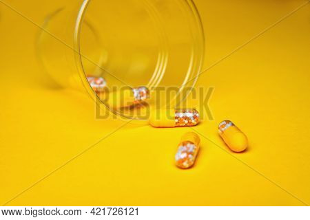 Capsules In A Glass Beaker. Medical Tablets, Vitamins In A Granule, In Yellow Capsules On A Yellow B