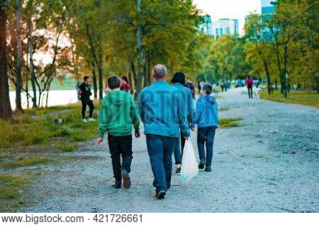 Family Walks In The City's Green Park. Relationship. Communication. Street. Walk. Strolling. Nature.