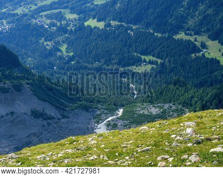 There Are Many Stones On The Grassy Slope. From The Slope You Can See Forests, Fields, A River And S