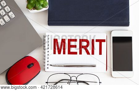 Merit Text On Notepad,pen, Office Tools On The White Background. Business