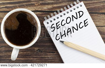 Second Chance Text On The Notebook With Coffee On Wooden Background