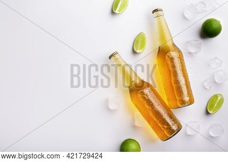 Two Full Transparent Glass Bottles With Ale Without Labels, With Flowing Drops, Lie With Ice And Pie