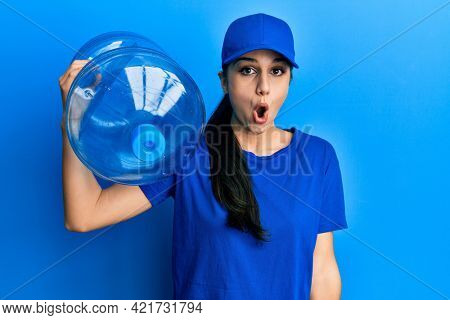 Young hispanic woman wearing delivery uniform holding water carafe scared and amazed with open mouth for surprise, disbelief face