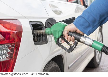 Man's Hand Holds Green Gas Pump In Car Tank During Process Of Refueling Car With Gasoline Or Diesel.