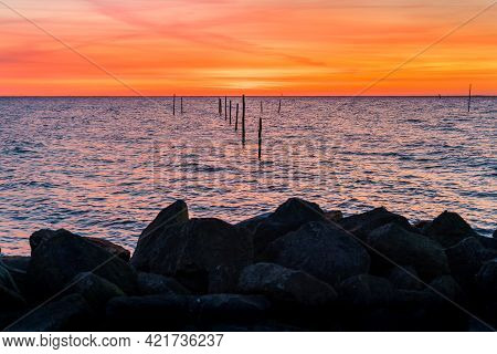 Setting Sun Above Dutch Ijsselmeer With Poles Of Fish Trap In Foreground, Lake Ijssel, Flevoland, Ne