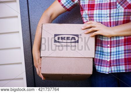 Tambov, Russian Federation - September 04, 2019 Woman With Ikea Cardboard Box Standing In Front Of T