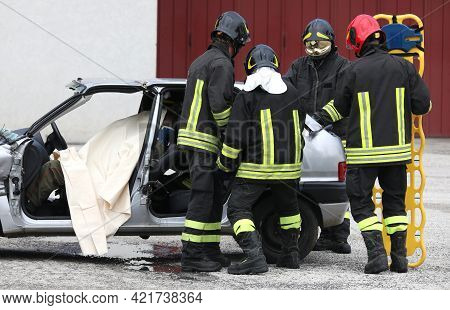 Teams Of Firefighters During The Rescue Of The Injured And The Stretcher To Transport Him To The Hos