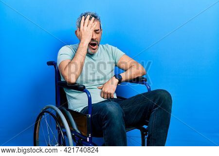 Handsome middle age man with grey hair sitting on wheelchair yawning tired covering half face, eye and mouth with hand. face hurts in pain.