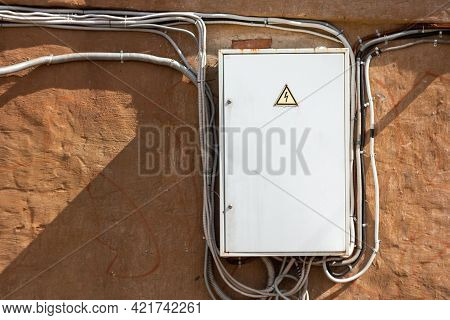 Electrical Switchboard With Cables On An Old Brick Wall. Photos On The Topic Of Electrical Safety An