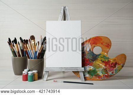 Easel With Blank Canvas, Brushes, Paints And Palette On White Wooden Table