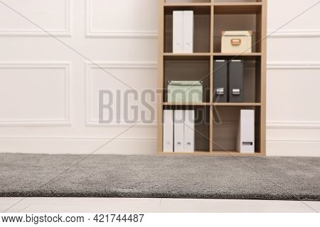 Room With Soft Grey Carpet, Shelving Rack And White Wall. Space For Text