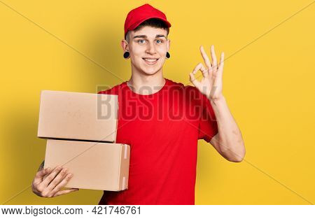 Young caucasian boy with ears dilation holding delivery package doing ok sign with fingers, smiling friendly gesturing excellent symbol