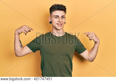 Young caucasian boy with ears dilation wearing casual green t shirt looking confident with smile on face, pointing oneself with fingers proud and happy.