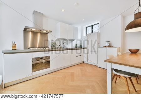 Interior Of Spacious Kitchen With White Cabinets And Stainless Extractor Hood And Black Counter