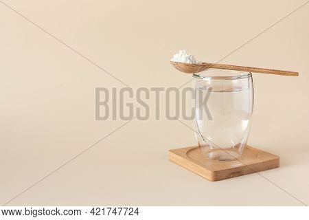 Protein Or Collagen Powder In A Spoon And A Glass Of Water On A Beige Background With A Copy Space.