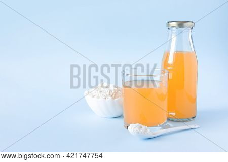 Protein Or Collagen And Orange Juice On A Blue Background. Food Supplement Concept. Natural Beauty A