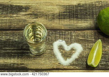 Salt Is Poured Onto The Heart-shaped Board. On The Board Are Salt, Lime And Tequila. Background With