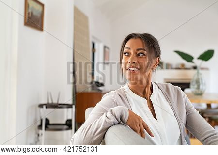 Thoughtful mature african woman sitting on couch at home and looking outside the window. Contemplative beautiful woman relaxing on sofa. Smiling mid adult woman with copy space contemplating.