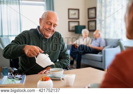 Smiling old man pouring hot tea in cup from kettle in nursing home. Happy disabled elder enjoying tea time in the afternoon together with other patient of the care facility. Elderly man in care centre