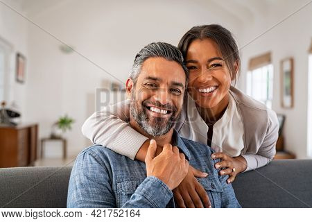 Portrait of multiethnic couple embracing and looking at camera sitting on sofa. Smiling african american woman hugging mid adult man sitting on couch from behind at home. Happy mixed race couple laugh
