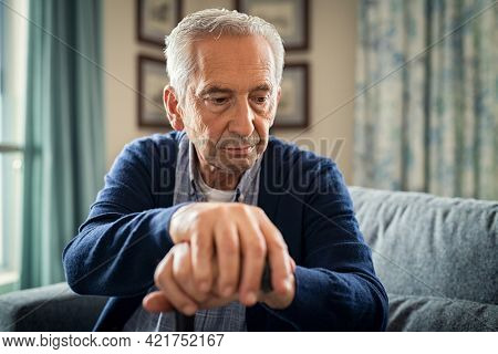 Depressed old man sitting at home while holding walking stick. Retired sad man holding wooden walking cane handle sitting alone at care facility. Elderly man suffering from loneliness and alzheimer.