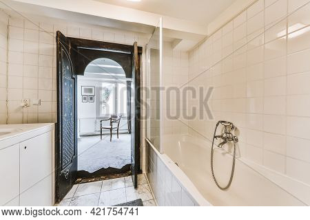 Interior Of White Tile Bathroom With Tub And Sink Cabinet And Opened Oriental Doorway Leading To Bed