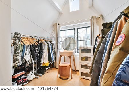 House Wardrobe Room With Small Table And Pouf Among Racks Of Clothes And Shoes On Floor