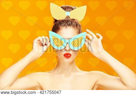 Pin-up style and beauty. Portrait of an exciting pretty woman posing in paper sunglasses and a bow in pin-up style on a yellow background with hearts. Makeup and cosmetics. Studio shot.