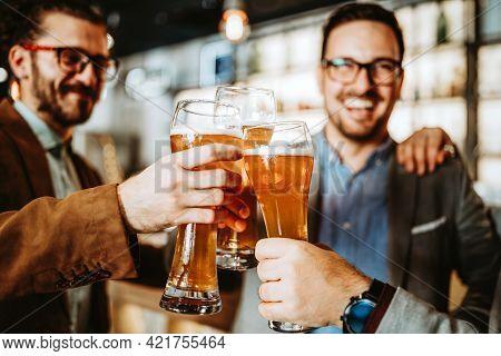 Business People Drink Beer After Work In Pub. Businessmen Enjoy A Beer.