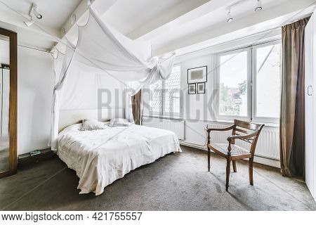 Interior Of Light Bedroom With Carpet Flooring And White Canopy Above Big Bed In Soft Daylight