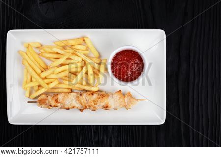 Grilled chicken shashlik meat with fried potatoes on white plate on black wooden background