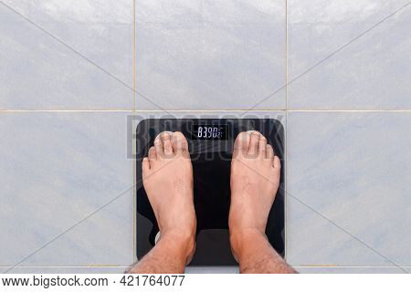 Man Weighs Him Self On A Digital Scale On Tiled Floor. Selective Focus On Electronic Display.