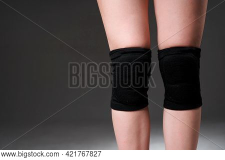 Womens Legs With A Knee Pad For Rehabilitation After Injuries. Close-up. Isolated On White Backgroun