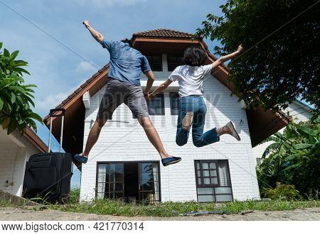 Happy Couple In Front Of The New Home On Moving In Day, And Start A New Life Family. Concept Of Home