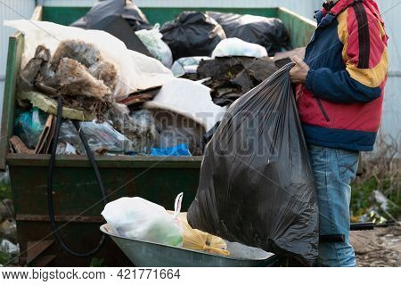 Young Man Throws Out A Large Plastic Garbage Bag To The Garbage Container Outdoors