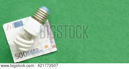 Energy-saving Lamp And Euro Banknote On Green Background, Copyspace.the Concept Of Saving Money In E