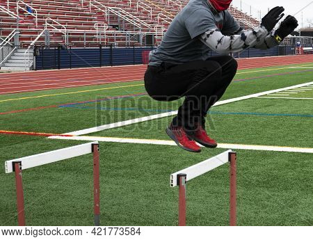 A Male High School Track Runner Is Jumping Over Hurdles On A Green Turf Field During Track And Field