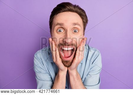 Photo Of Shocked Funny Young Guy Wear Denim Clothes Arms Cheeks Open Mouth Big Eyes Isolated Purple
