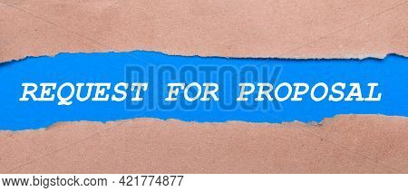 A Strip Of Blue Paper With The Inscription Request For Proposal Between The Brown Paper. View From A
