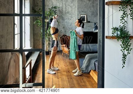 Slender Mature Woman Changes Clothes Near Window In Loft Apartment, Her Sister Helps Her.