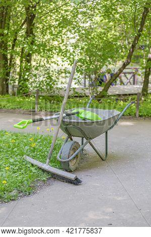 Old Gray Garden Wheel Barrow In A Summer Park