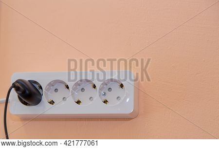 A Socket With A Black Plug Stuck Into It On A Beige Wall. Electrical White Elements Are Mounted Hori