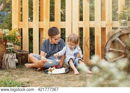 Kids Resting Together At Camping Site In Summer. Joyful Boys Having A Picnic. Children Cooking In Co