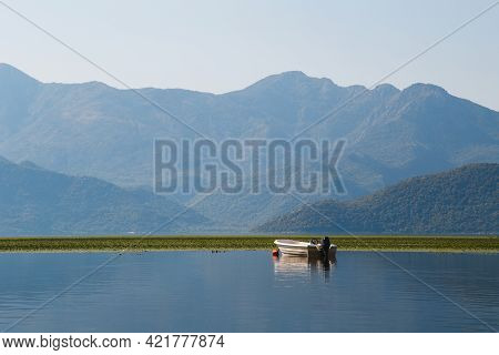 A Beautiful View At A Lonely Boat In The Middle Of The Lake Skadar With Blue Mountain View At Backgr