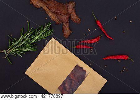 Jerky Snacks, Red Papper, Rosemary And Craft Package On Black Background. Mockup. Dried And Spiced M